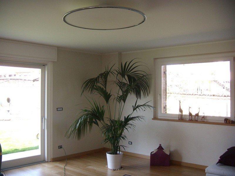 Lampadario tondo e piatto in una stanza dalle grandi vetrate e con una pianta