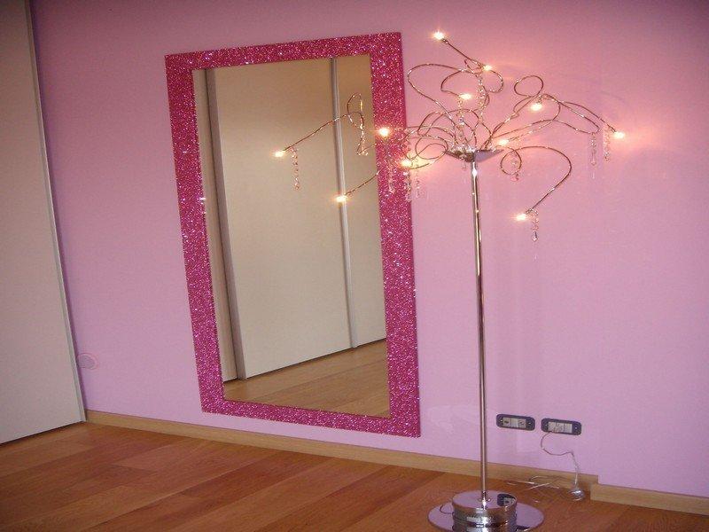 Lampada da terra di design in una stanza rosa con grande specchio rosa luccicoso