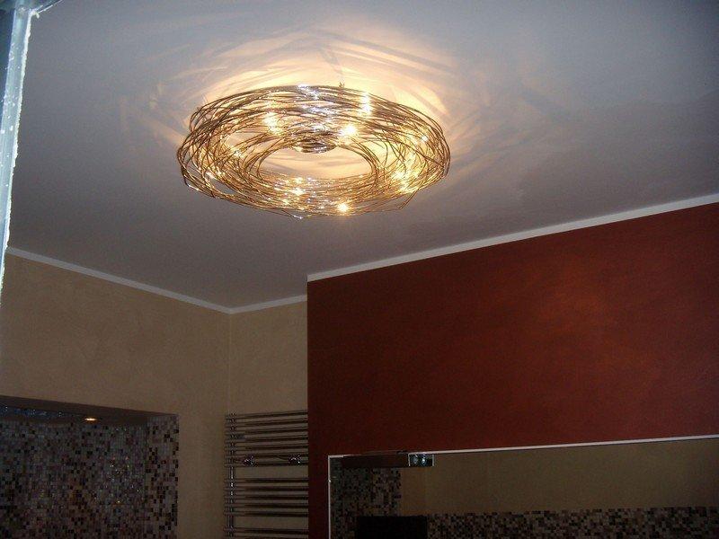 lampadario di design acceso in un camera da letto privata