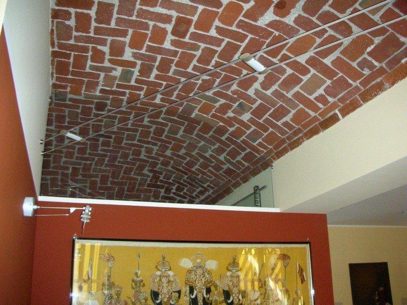 soffitto mattonato di un museo con illuminazione a faretti