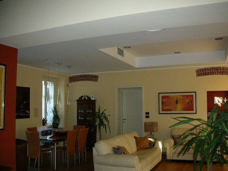 Soggiorno privato con divano bianco, tavolo da pranzo con 6 sedie e 3 lampadari moderni per l'illuminazione