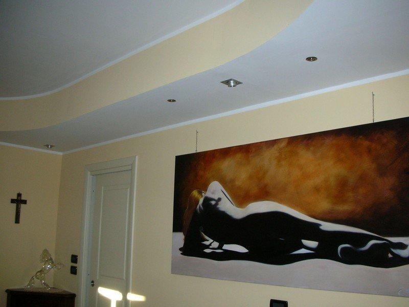 Illuminazione a faretti in una camera da letto privata con grande quadro