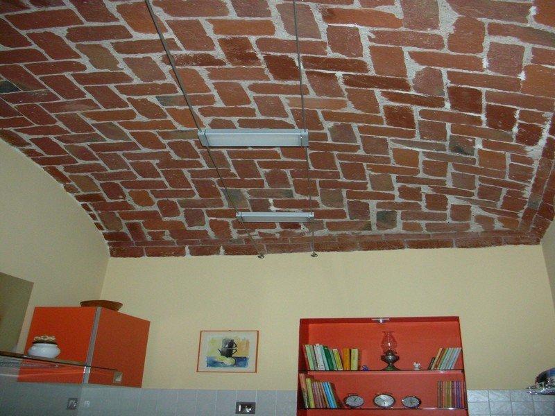 Illuminazione moderna con faretti in un soggiorno privato con soffitto in mattoni