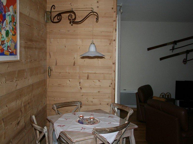 Lampadario bianco in un soggiorno rustico con tavolo, sedie e poltrone
