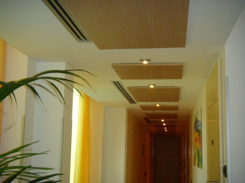 lungo corridoio bianco illuminato da faretti