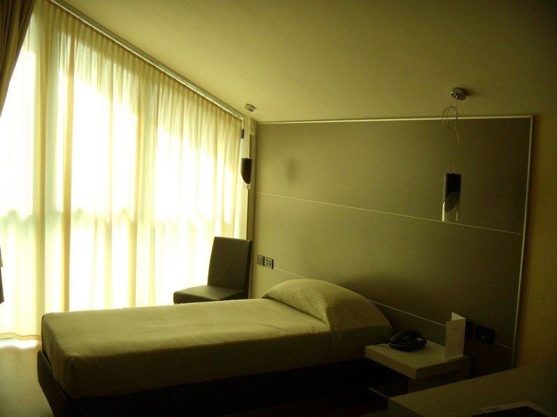 Camera d'albergo con letto singolo, ampia finestra coperta da tenda e lampadari moderni