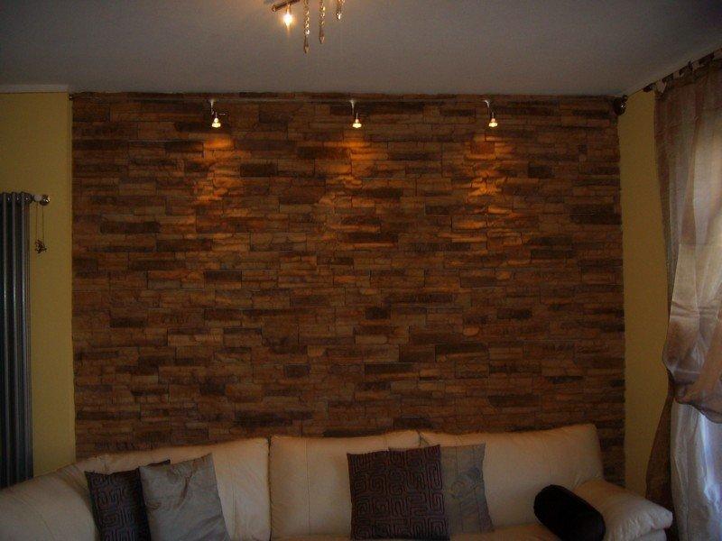 soggiorno con divano bianco e cuscini marroni, parete in pietra e faretti moderni per l'illuminazione