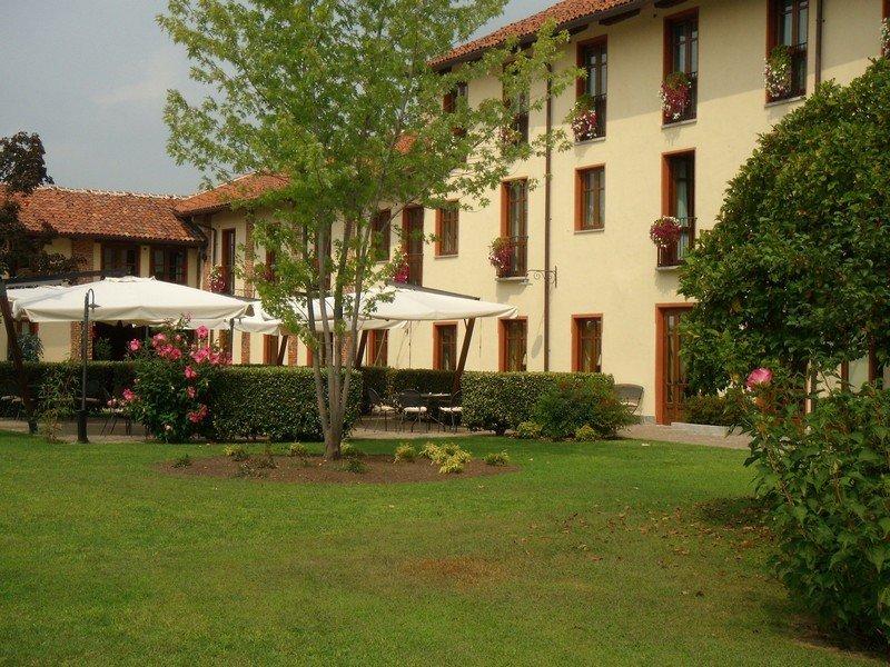 vista del giardino di un albergo con ombrelloni, alberi, siepi, ed illuminazione da esterni