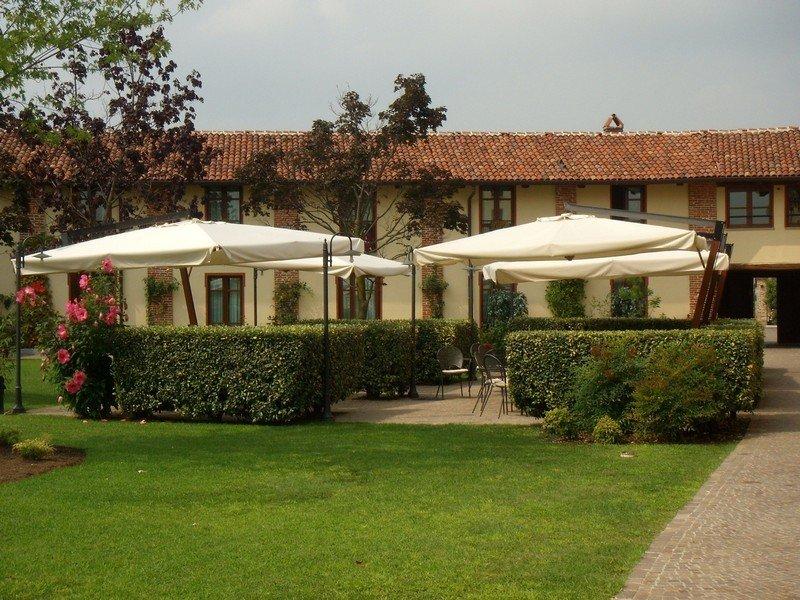 Esterno di un ristorante con ombrelloni, siepi e illuminazione da esterno