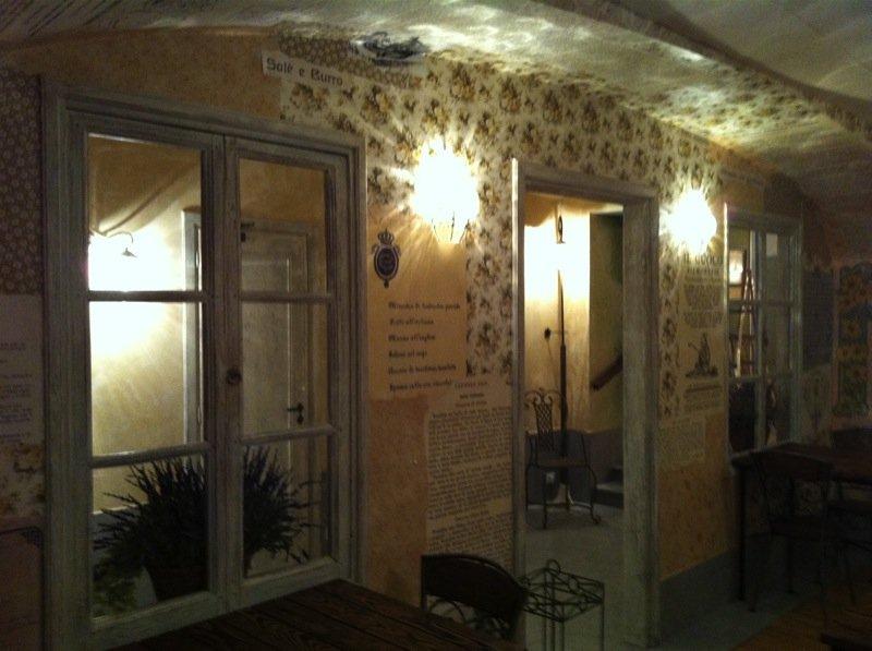 Ingresso di un ristorante con tavoli, sedie e finestre e con illuminazione da esterni