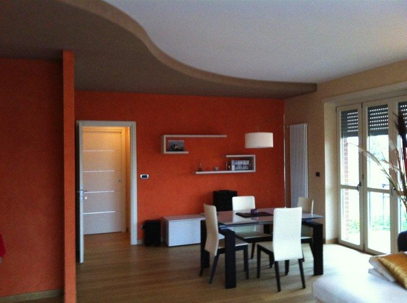 sala da pranzo privata, arredata in stile moderno, con pareti arancioni e grande lampada da terra