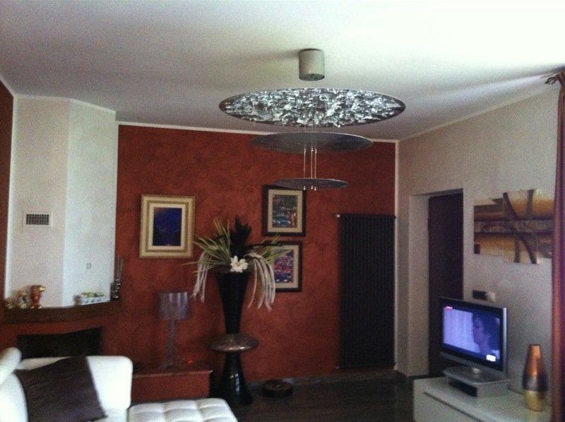 soggiorno privato arredato e illuminato da un grande lampadario a cerchi