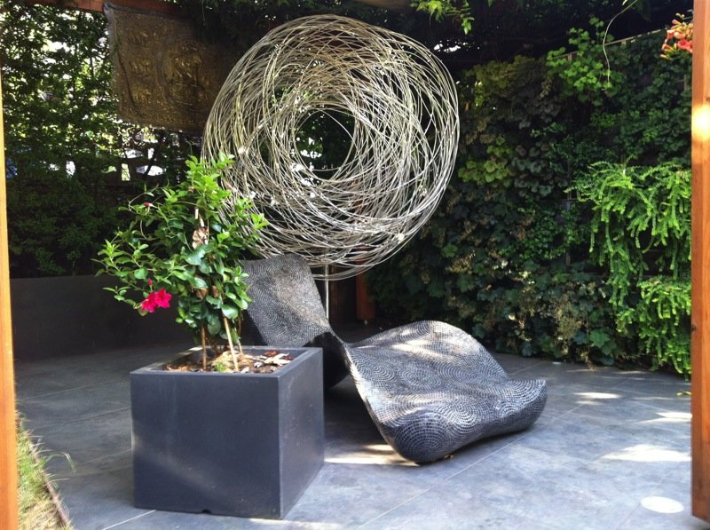 Giardino privato con lampada da terra per esterni, poltrona di design e vaso con pianta