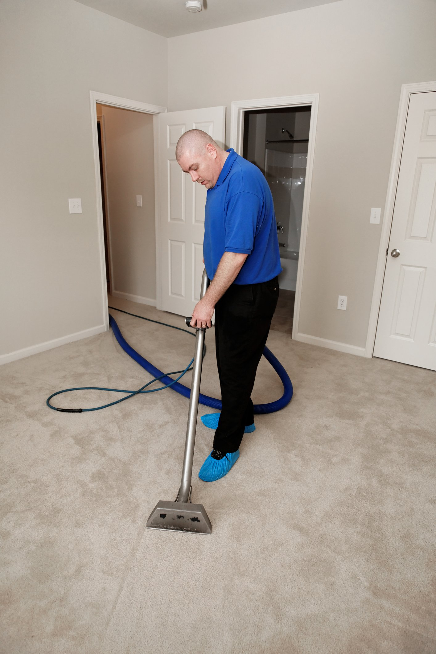 Gray carpet with extended arm vacuum on it
