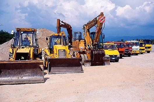 Motori di terra e di altri macchinari di auto in fila alla zona di costruzione