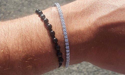Mano di un uomo con un bracciale di perline nere, un'altra con perline bianche