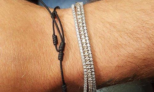 Mano di un uomo con tre bracciali di perline molto fini e un bracciale nero realizzato con un filo