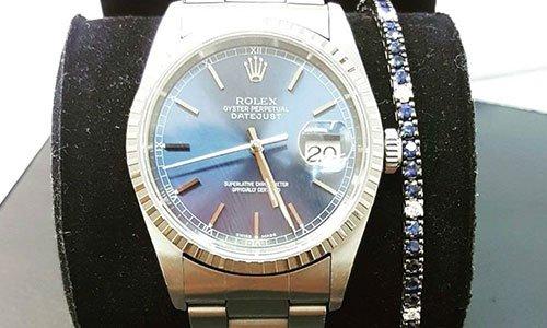 Porta orologio con orologio marca Rolex e un bracciale con perline blu e bianche