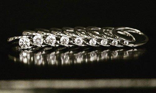 Rappresentazione simile ad anelli argentati l'uno accanto all' altro e davanti una fila di perline brillantate