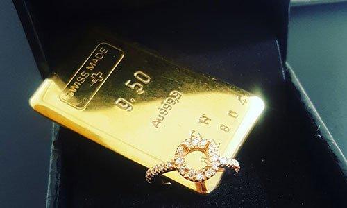 Una scatola con anello d'oro con perline brillanti e un lingotto d'oro con scritto g.50, Au 999.9