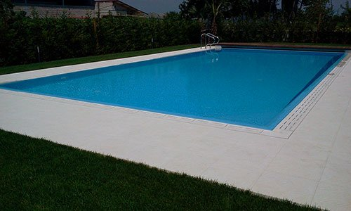 piscina in un giardino circondato da siepi