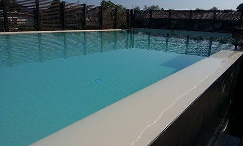 piscina all'interno di un giardino circondato da steccato in legno