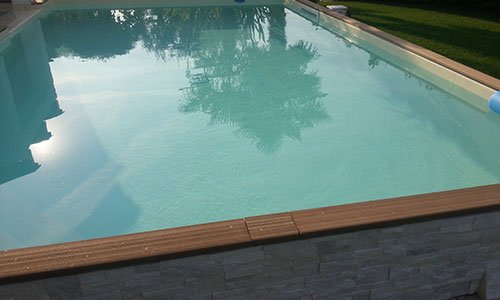 piscina rialzatacon mattoni in pietra e bordi di legno