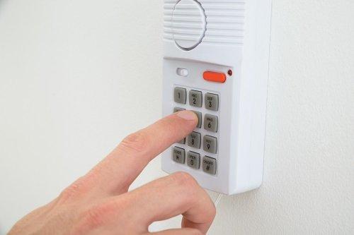 una mano con una cornetta che digita i tasti sulla tastiera di un telefono fisso