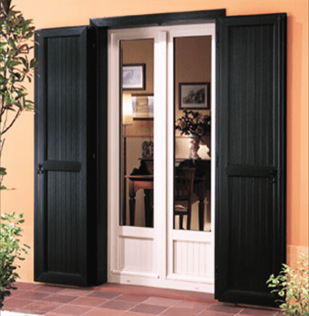 una porta finestra con le ante delle  persiane aperte in legno di color verde