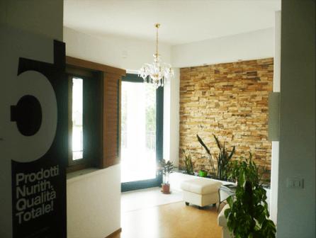 un pannello con scritto prodotti Nurith qualità' totale e vista di una sala con un pouf bianco e dei vasi con delle piante