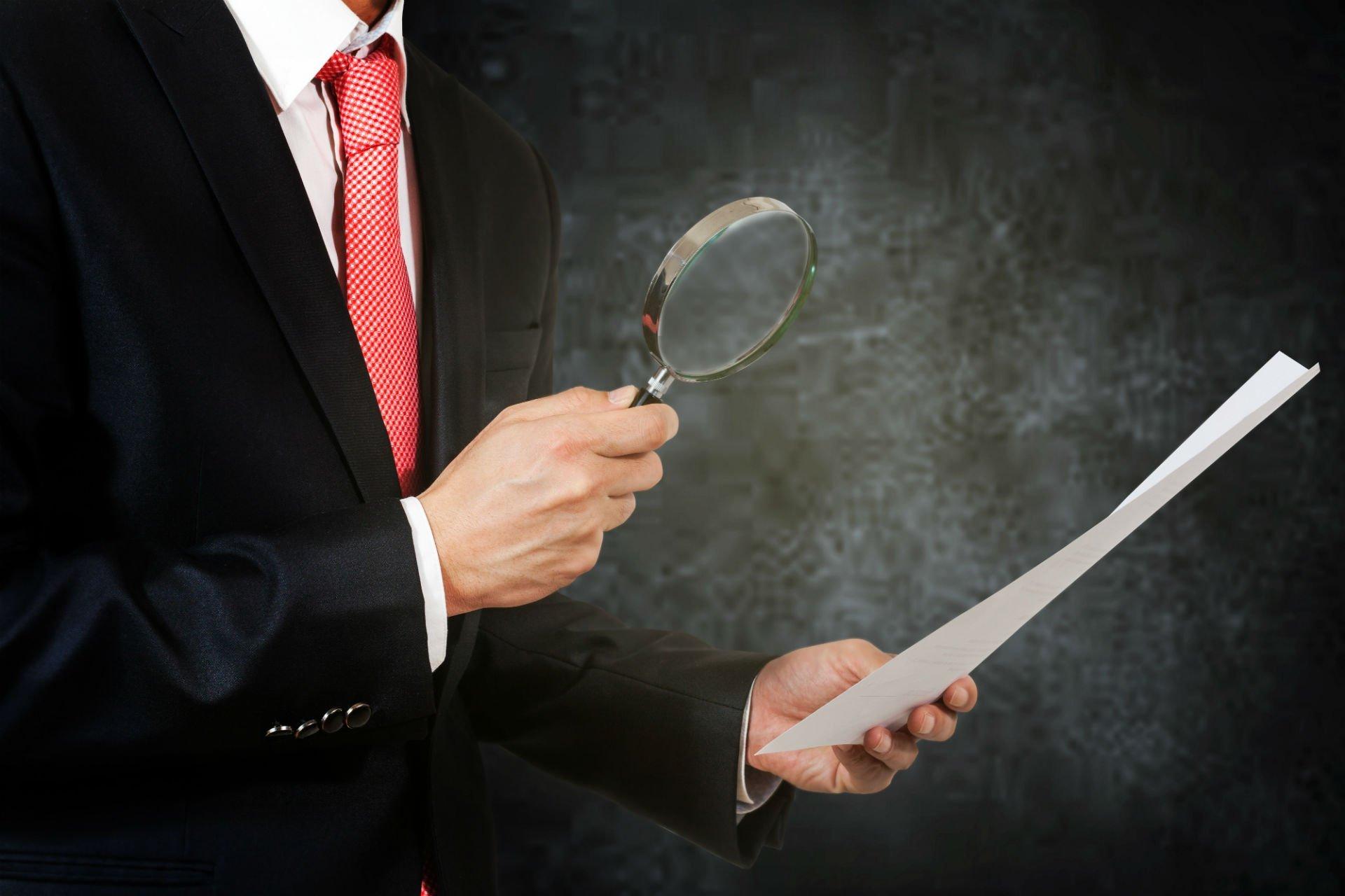 un uomo con una lente di ingrandimento e un foglio in mano