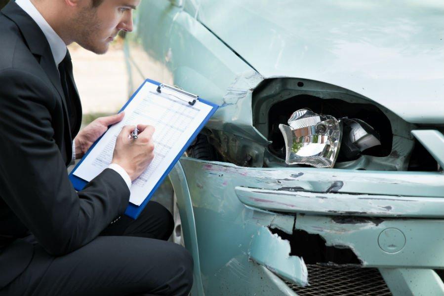 un perito che compila una scheda tecnica è accanto una vettura incidentata
