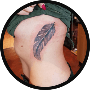 Tattoo of a feather above a woman's waist