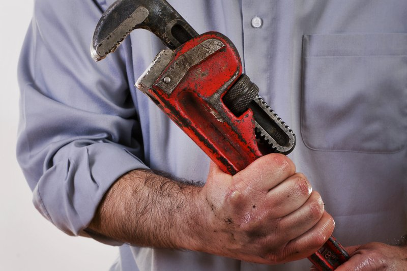 Plumber firmly holding a wrench