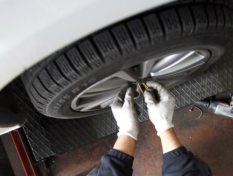 tecnico mentre monta la gomma di un'auto