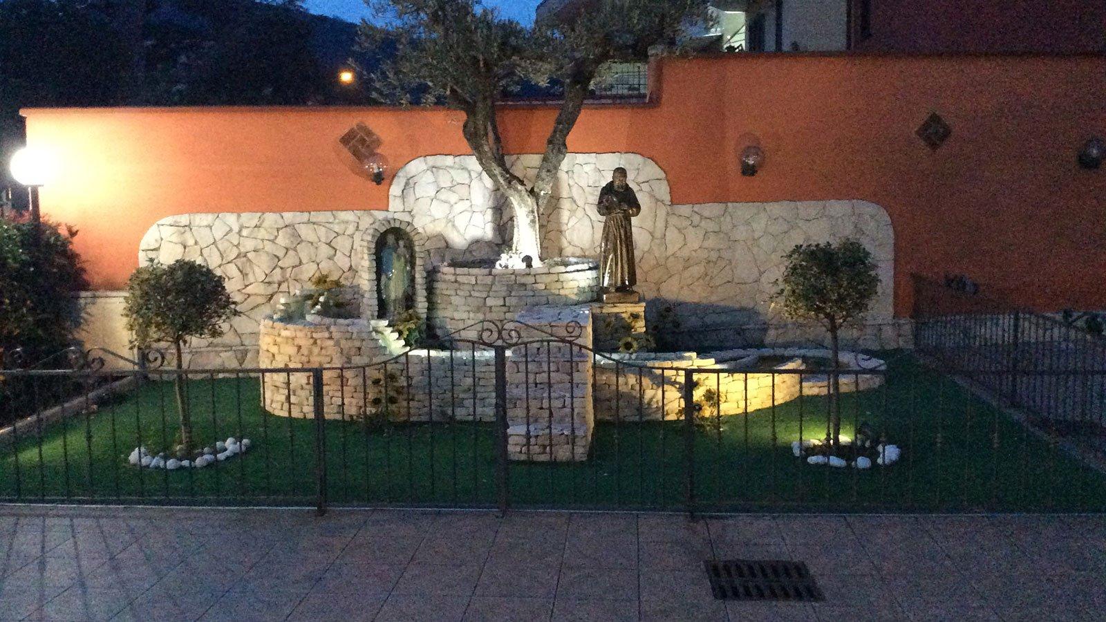 un'aiuola con una piccola costruzione in pietra e delle figure religiose