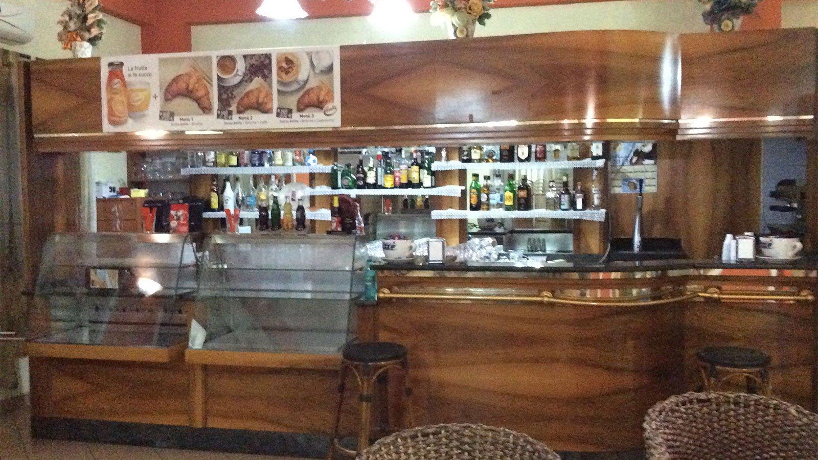 vista del banco di un bar e delle bottiglie di liquori dentro a degli scaffali