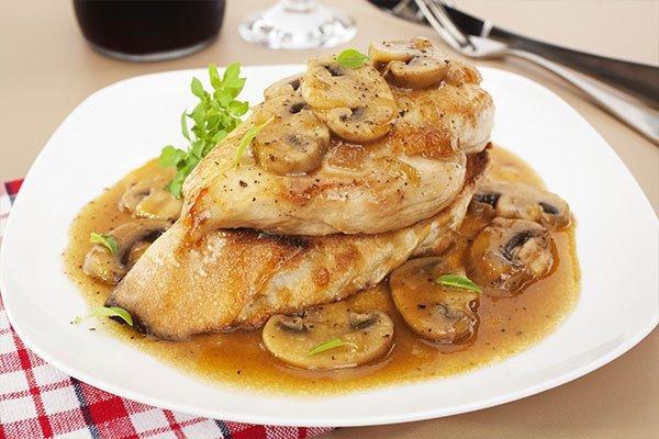 un piatto con petto di pollo, funghi e del sugo