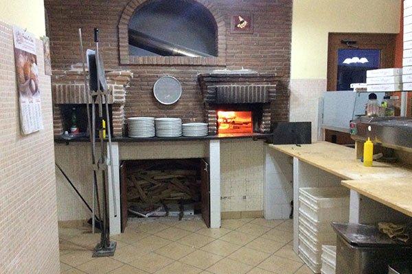 vista del forno a legna, del banco da lavoro e dei piatti