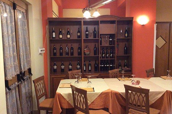 vista di un tavolo e dietro un mobile con delle bottiglie di vino