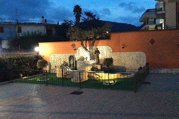 una piccola costruzione in pietra e delle figure religiose in un giardino