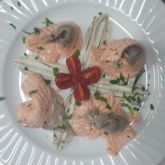un piatto a base di carpaccio di pesce e filetto e un pomodorino tagliato a fiore