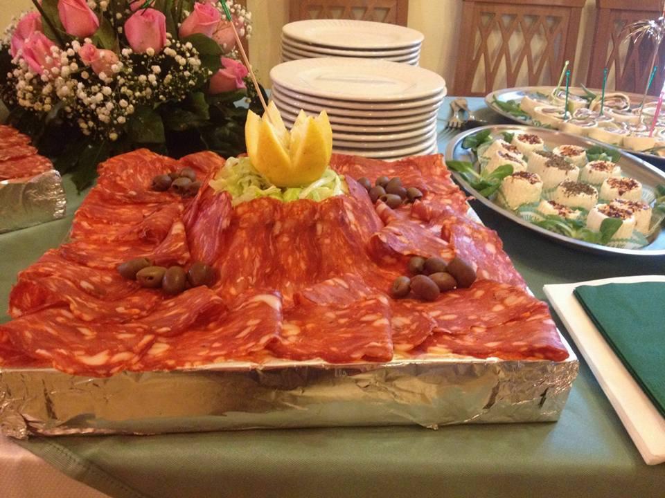 un vassoio con del salame a fette, olive e decorazione al centro con del limone