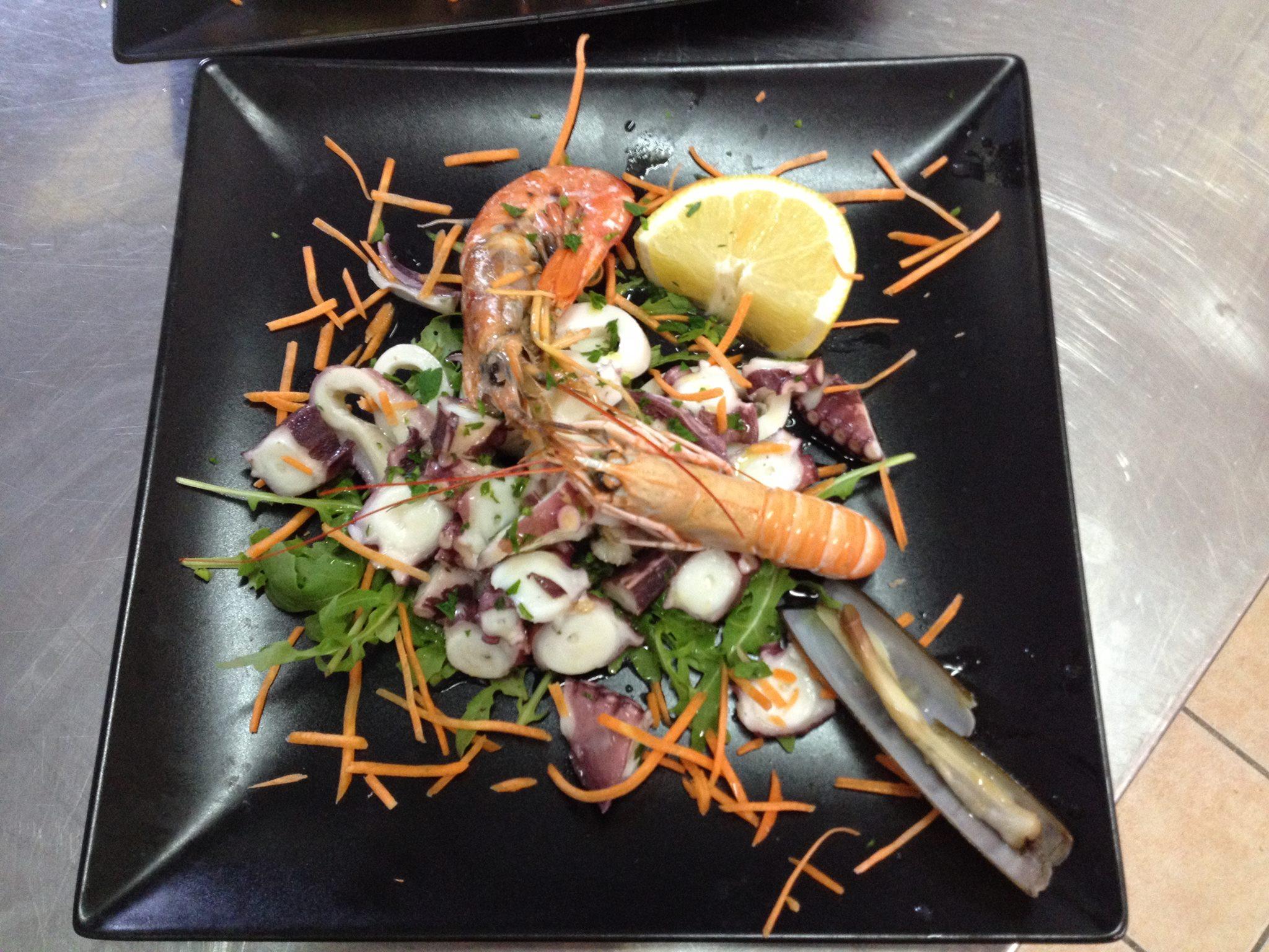 un piatto a base di scampi, insalata e polipo