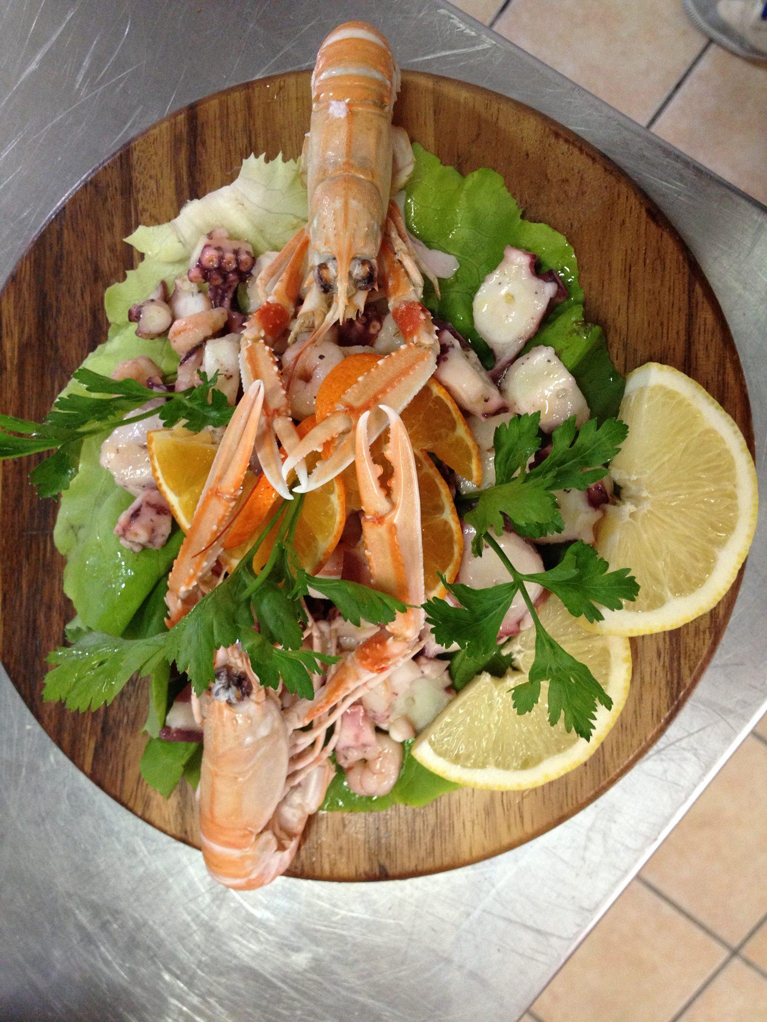 un tagliere con dell'insalata e del pesce