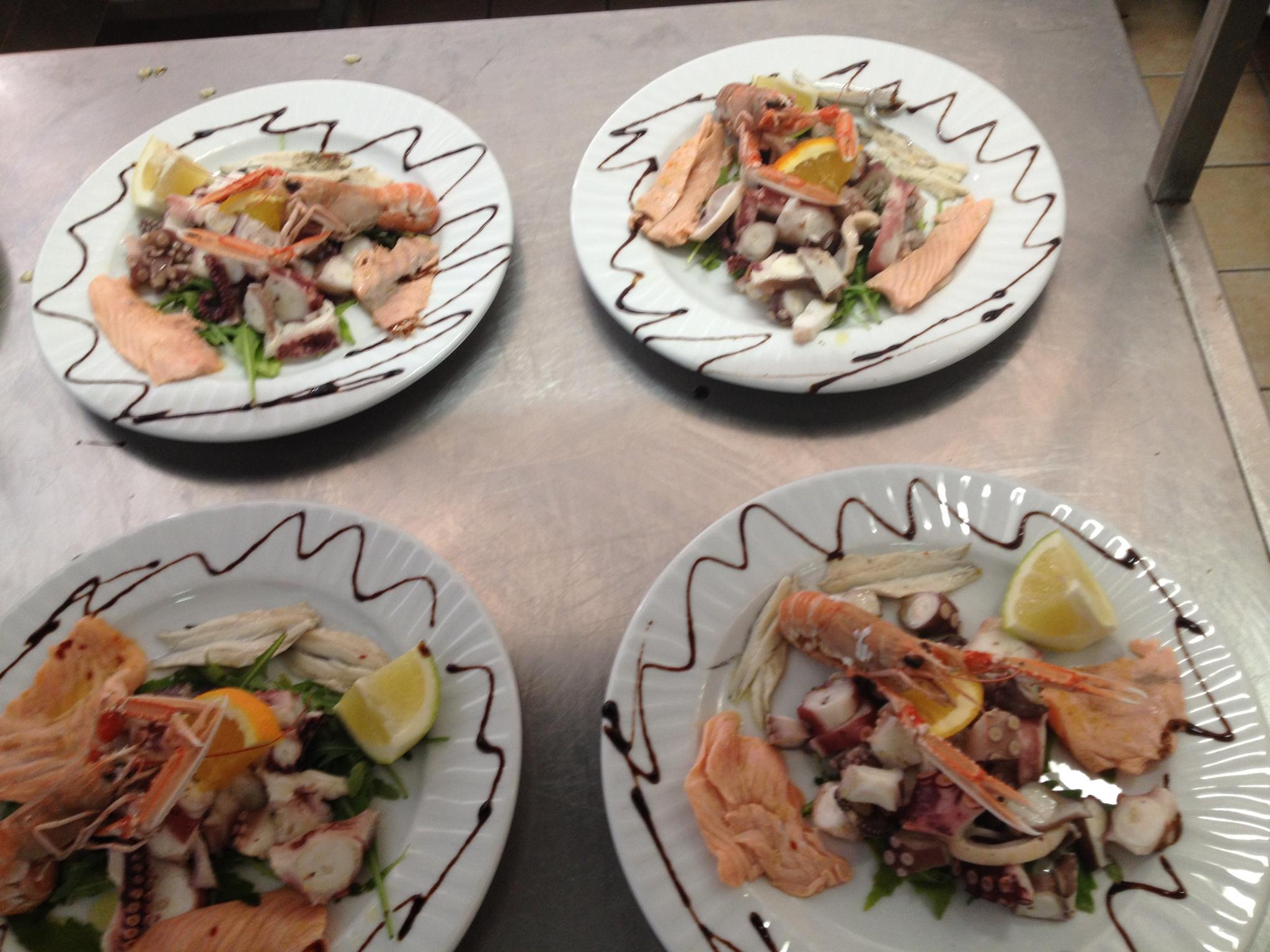 quattro piatti a base di carpaccio di salmone,polipo e scampi