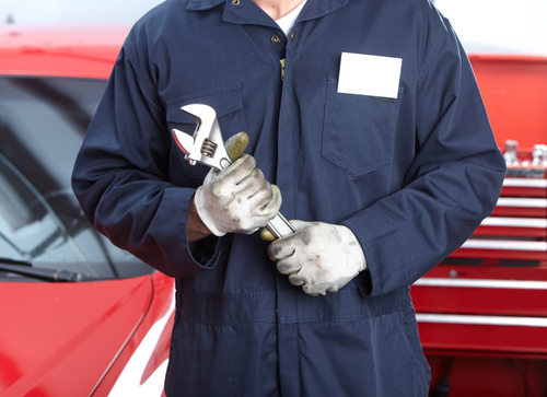 Car mechanic with wrench ready for transmission services in Milford