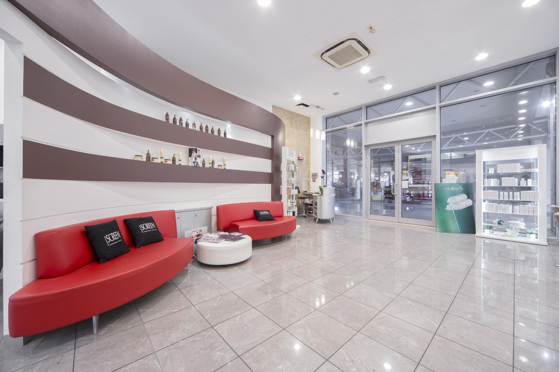 bancone del salone di parrucchieri e divani rossi