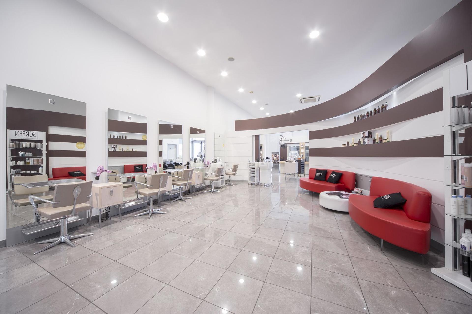 interno del salone di parrucchieri con postazioni e divanetti
