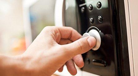 someone adjusting a microwave timer